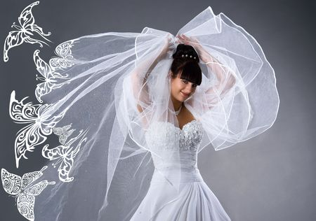 Schöne Braut in einem weißen Kleid mit Schmetterlingen. Studioaufnahme