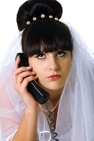 Sad bride speaks on the phone. Studio shot photo