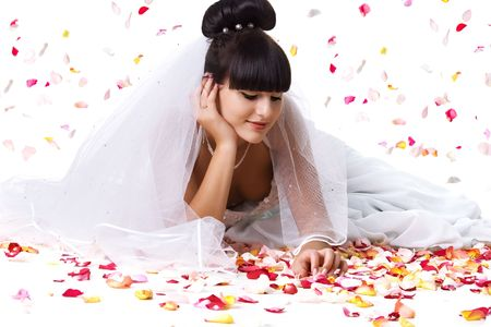 Beautiful bride in a white dress with rose petals. Studio shot photo