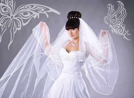 Beautiful bride in a white dress with butterflies. Studio shot photo