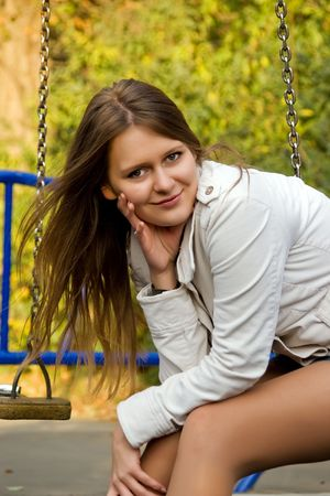 Portrait of a beautiful smiling  young woman on the swing photo