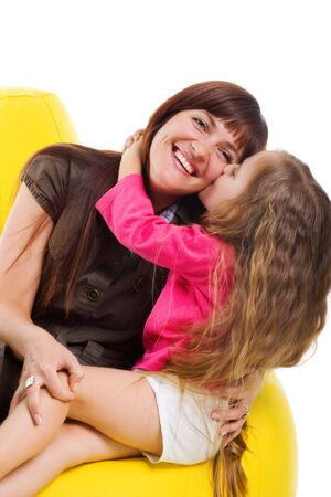 Cute little girl kiss her smiley mother. Studio shot Stock Photo - 5852189