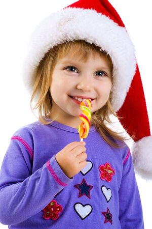 Little girl in santa claus hat with a bright lollipop photo