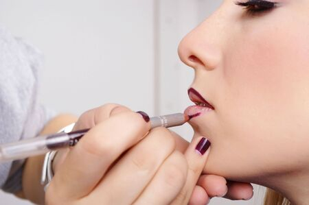 artist's model: Makeup artist tracing red contour on the lips of a girl Stock Photo
