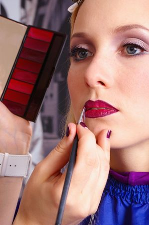 Makeup artist tracing red lipstick on the lips of a girl photo