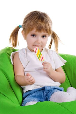 Little girl with a bright lollipop sit on green armchair photo