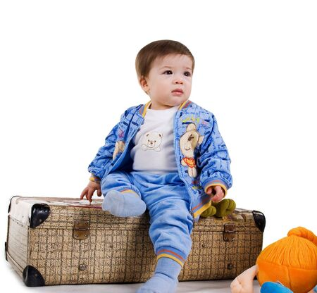 Cute little boy sit on a suitcase. White background photo
