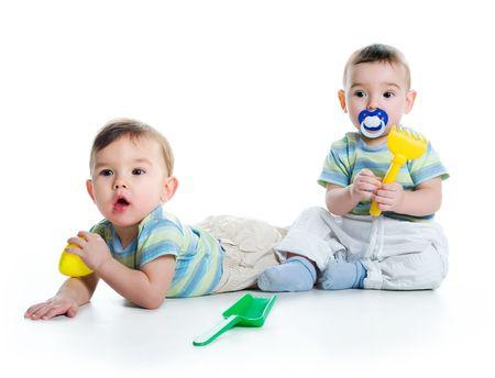 gemelas: Hermanos gemelos con pala y râteau aislado en un fondo blanco