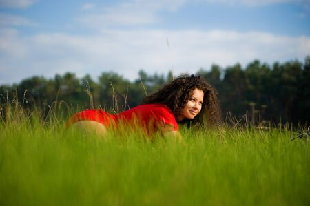 Very pretty woman in red on the grass photo
