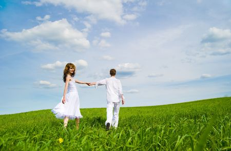 Couple holding hands in a flower field photo