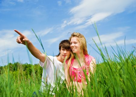 Couple sit in a green grass photo