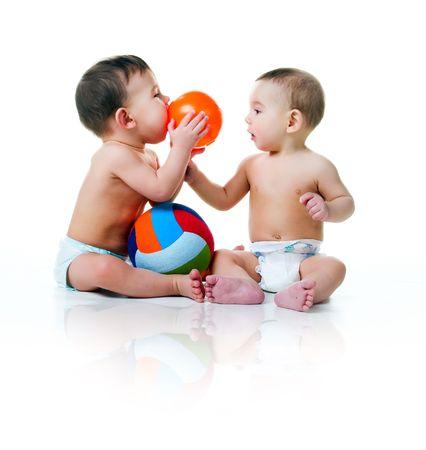 Dos hermanos gemelos con bolas aislados en un fondo blanco