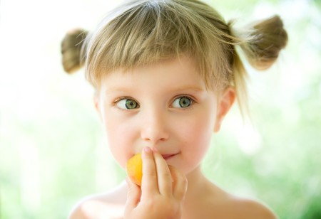 Close-up portrait of a cute liitle girl with the apricot photo