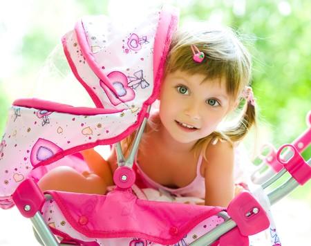 petite fille avec robe: Mignonne petite fille avec son transport jouet  Banque d'images