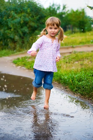 Girl junps barefoot in a puddle splashing water in the rain Stock Photo - 7415459