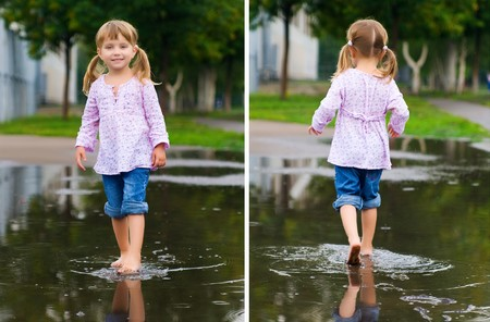 water play: Girl to walk barefoot in a puddle splashing water in the rain