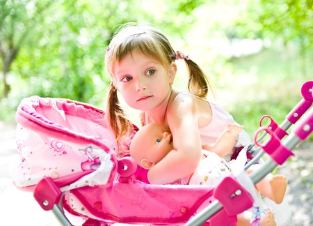 dolls: Cute little girl with her toy carriage