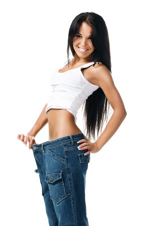Woman demonstrating weight loss by wearing an old pair of jeans photo