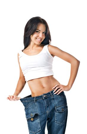 Woman demonstrating weight loss by wearing an old pair of jeans Stock Photo - 7803494