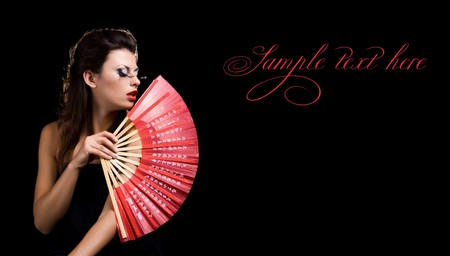 Beautiful woman with fan on  black background photo