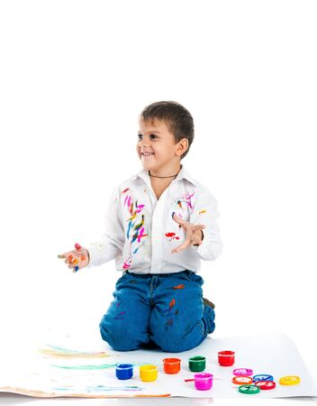 Adorable 3 year old boy covered in bright paint. photo