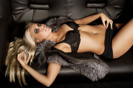Beautiful model dressed in fur laying on sofa photo
