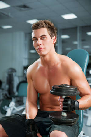 muscular build: A young man working out in a gym