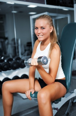 A young women lifting free weights with a confident smile photo