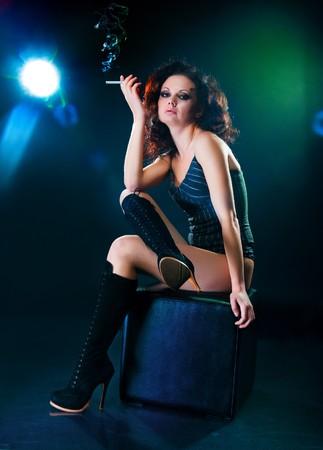 Beautiful young woman on black background smoking photo