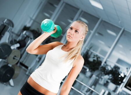 A young women lifting free weights with a confident smile Stock Photo