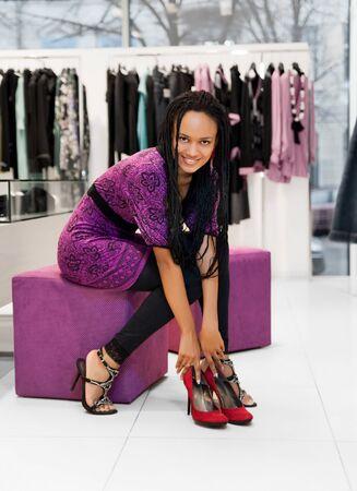comprando zapatos: Mujeres j�venes que tratan sobre el nuevo calzado jogging en la tienda  Foto de archivo