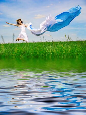 Happy young woman jumps. Sky as background photo