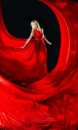 Perfect blonde in a red dress on black background photo