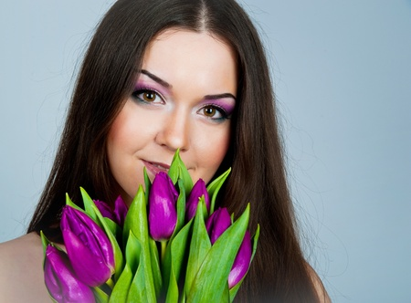 Cute young women with the flowers over grey backgroung photo