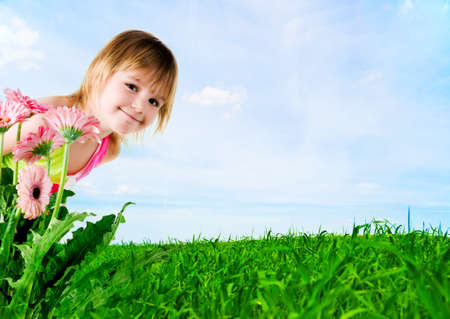 Cute little girl on a meadow background photo