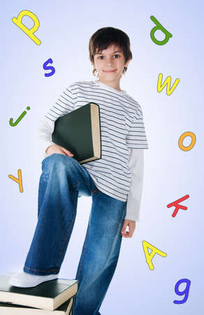 Cute little boy near the stack of big books on white background photo