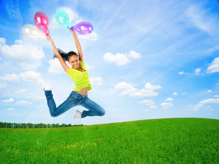 happy jumping young woman with balloons outdoor on a summer day photo