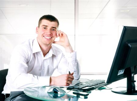 Happy businessman sits at the computer photo