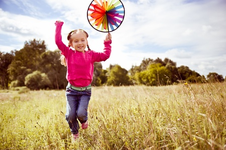 pinwheel: Girl on grass in summer  day Stock Photo