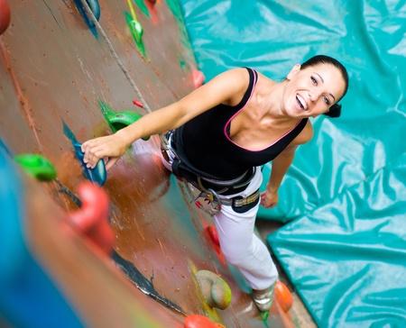 niño trepando: las mujeres de escalada en una pared Foto de archivo