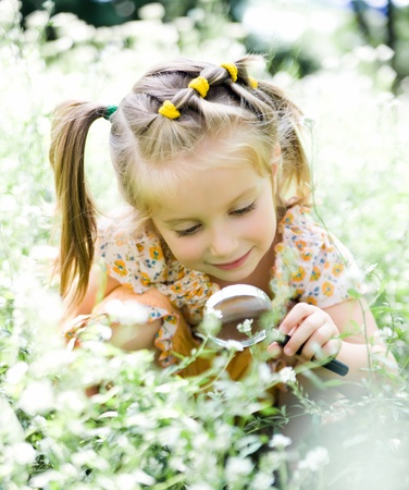 field glass: Little girl with magnifying glass looks at flower