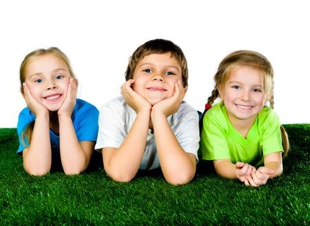 lying on grass: boy and girls lying on a green grass