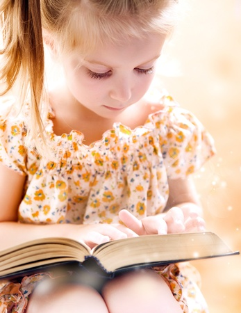 sweet happy little girl reading a book photo