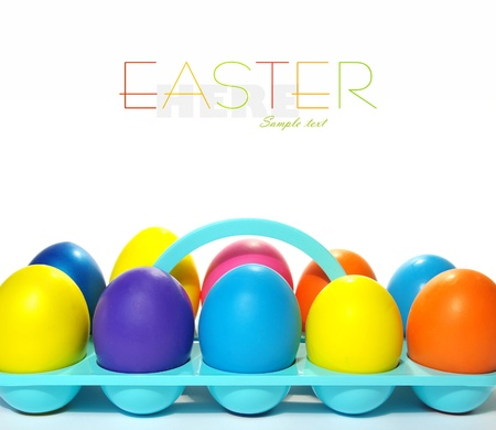 Easter holiday. Color eggs in a tray on white  background. photo