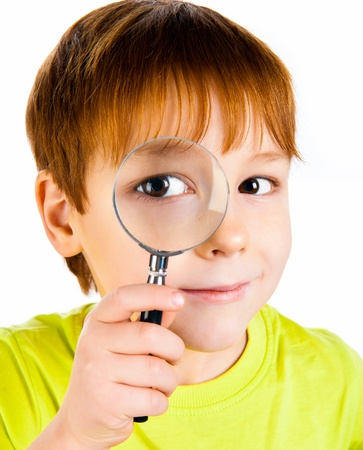 little boy looking through a magnifying glass Stock Photo