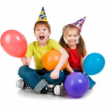 Niños con gorros de cumpleaños en el fondo blanco