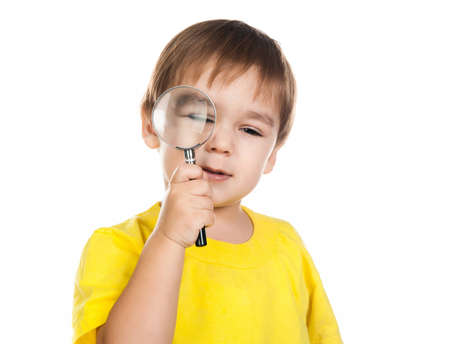 little boy looking through a magnifying glass photo