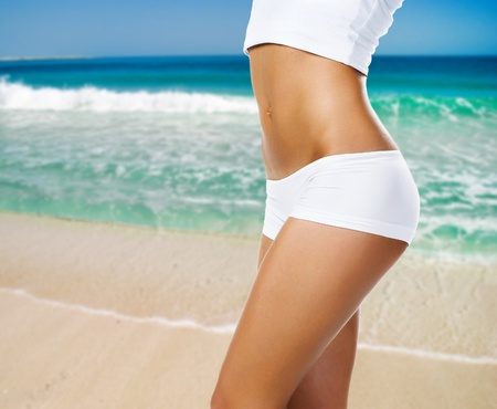 Female body  on a beach  background photo