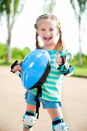 niño en patines: Niña en patines de ruedas en un parque