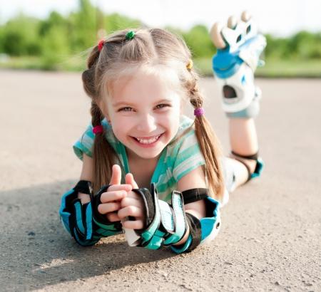 Little girl in roller skates at a park photo